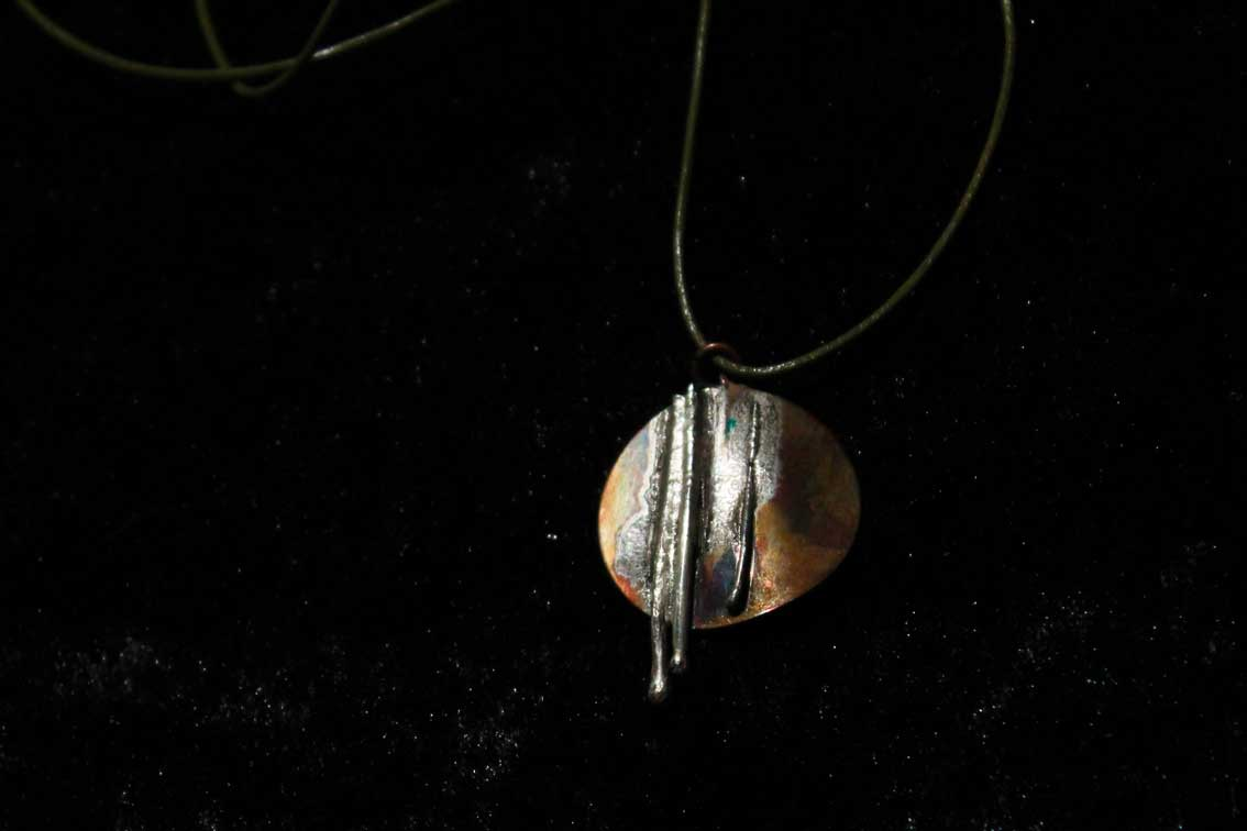 circular copper pendant with three lengths of silver wire fused to it's surface
